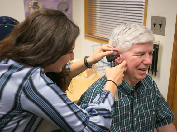 A graduate clinician uses an otoscope to look into an adult client's ear