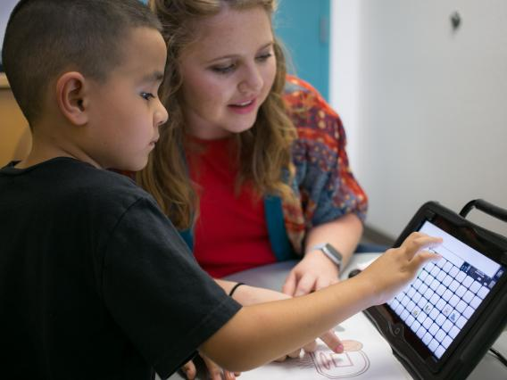 A young client uses his alternative and augmentative communication device